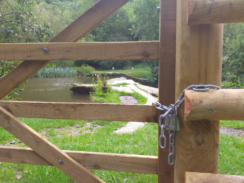 A chained and padlocked access gate in the new fencing sealing off access to the weir in the Monsal valley